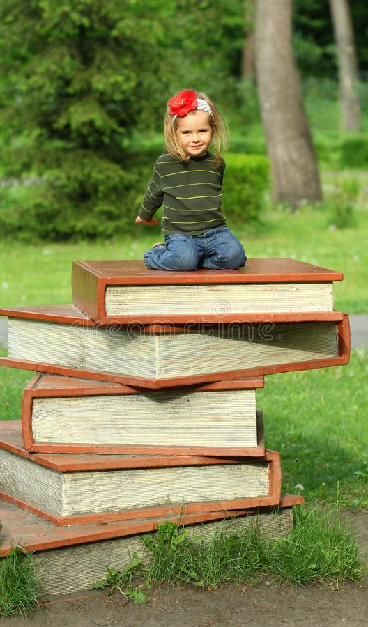 Book festival in the public park, toddler girl sitting on a giant pile of books. Bucha, Ukraine - 6 May, 2018: Book festival in the public park, toddler girl royalty free stock photography