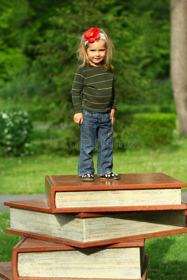 Book festival in the public park, toddler girl standing on a giant pile of books. Bucha, Ukraine - 6 May, 2018: Book festival in the public park, toddler girl royalty free stock photos