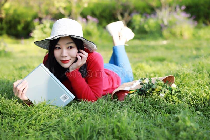 book flickaavläsning Blond härlig ung kvinna med boken som ligger på gräset utomhus- solig dag royaltyfria bilder