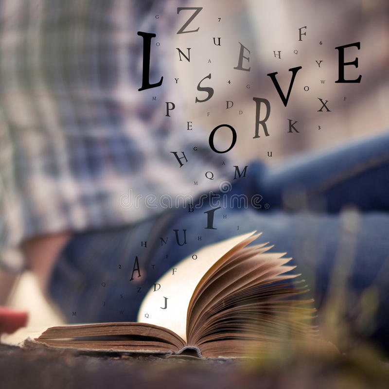 Download Book With Floating Letters In The Air Stock Photo
