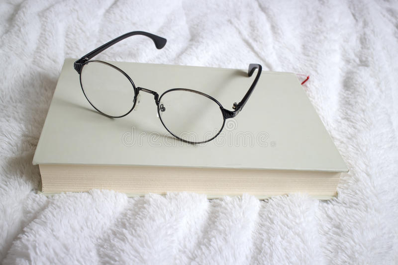 Book and glasses on a bed stock images