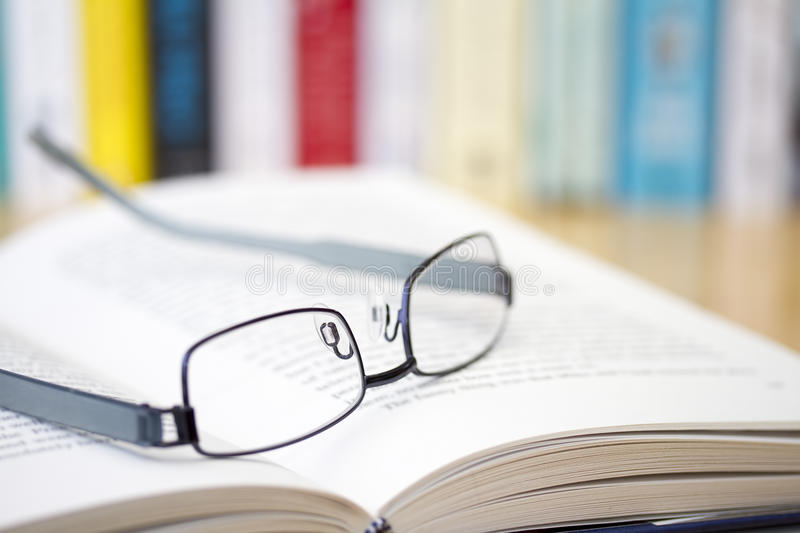Book with glasses on desk royalty free stock images