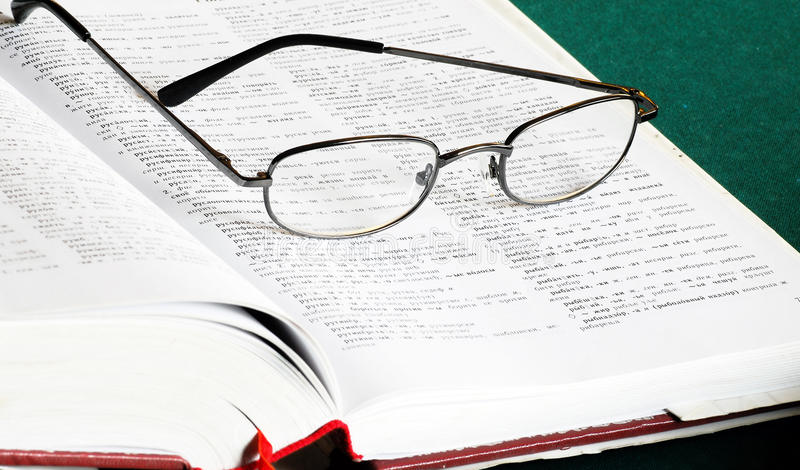 Book and glasses. Opened russian-serbian dictionary book with eye glasses stock photo