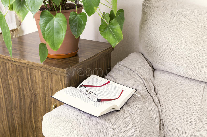 Book and glasses on the top of the arm of a sofa royalty free stock photo
