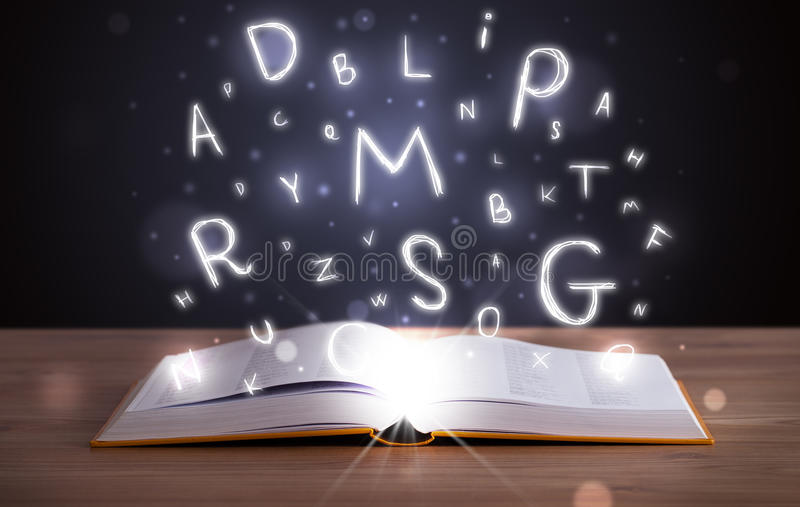 Book with glowing letters flying out on wood deck. Open book with glowing letters flying out on wood deck stock photos