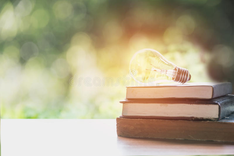 Book and glowing light bulb over it. Knowledge and education. Concept royalty free stock image