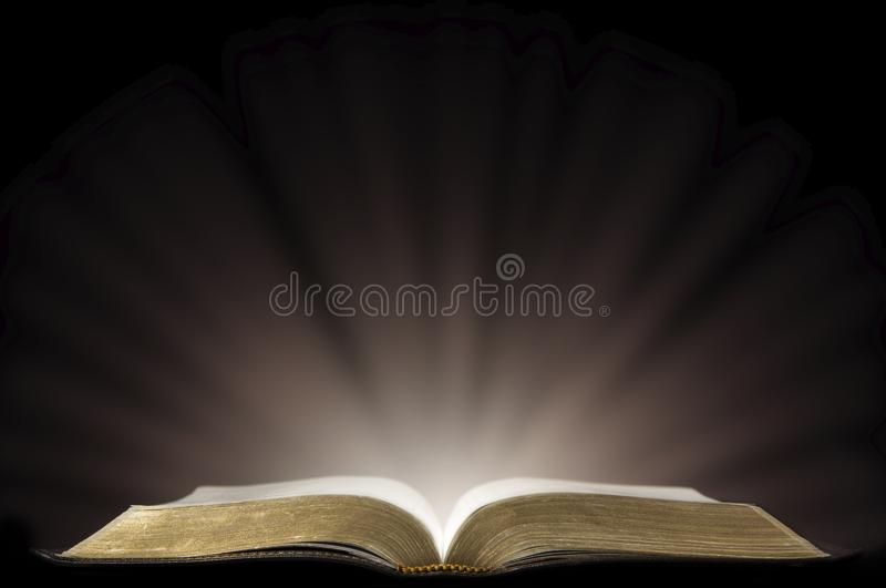 A Book that looks like a Bible Open in a Dark Room. With Light Pouring Out of it representing enlightment royalty free stock photos