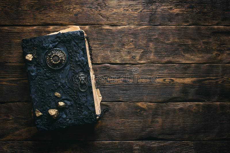 Book of magic. Ancient magic book on a wooden table background with copy space. Spellbook stock images