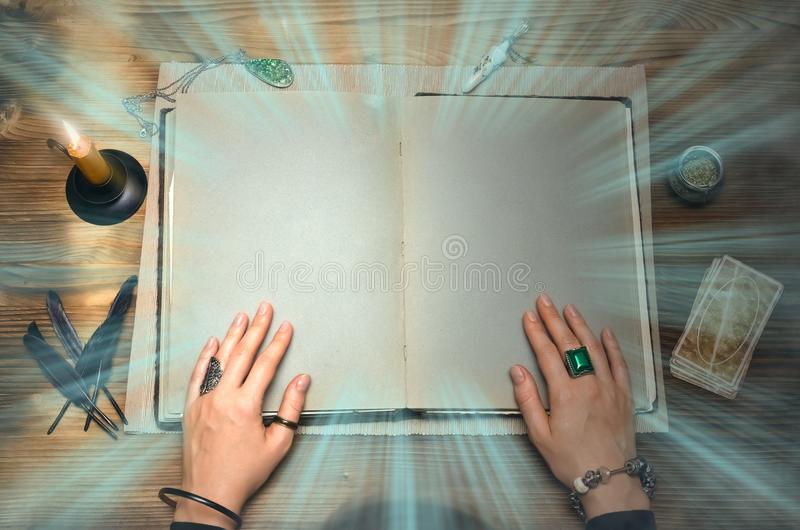 Book of magic. Future reading. Tarot cards on fortune teller concept. Book of magic with mystical light and copy space. Tarot cards on fortune teller desk table royalty free stock photo