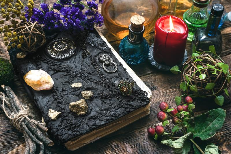 Book of magic. Spell book, magic potions and other various witchcraft accessories on the wizard table background royalty free stock photos