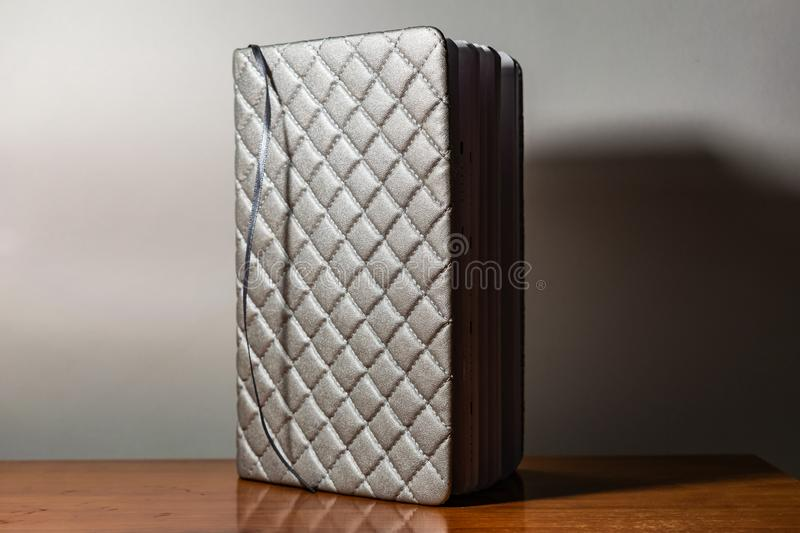 A book, a notebook with a checkered pattern on a wooden table in different poses. The cover is grey and soft with texture. Square royalty free stock image