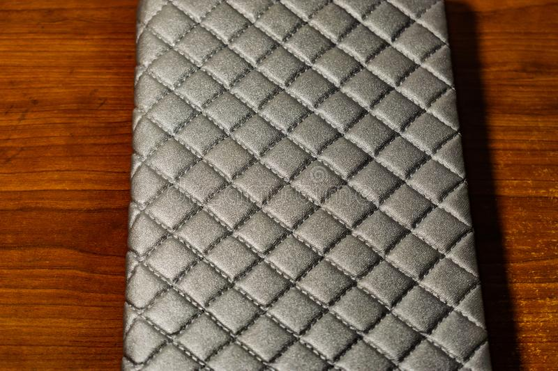A book, a notebook with a checkered pattern on a wooden table in different poses. The cover is grey and soft with texture. Square stock photography