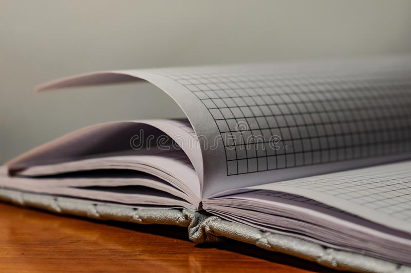 A book, a notebook with a checkered pattern on a wooden table in different poses. The cover is grey and soft with texture. Square stock image