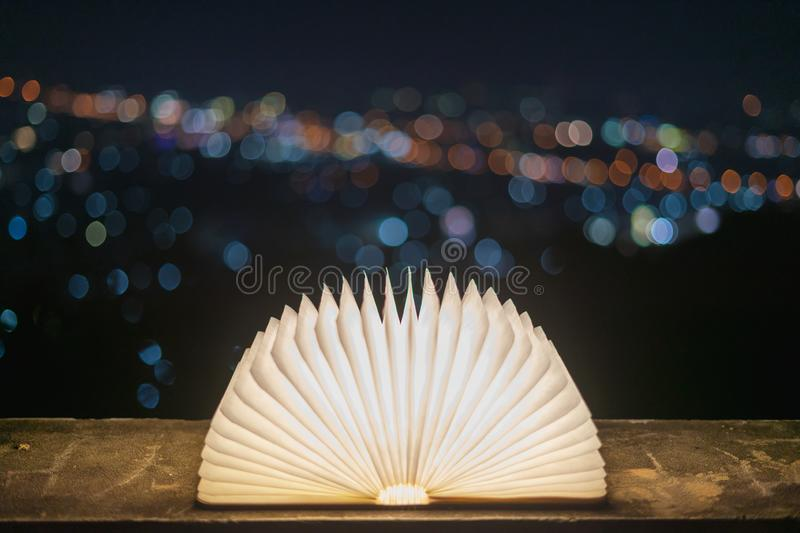 A book that opens with light on a paper like magic, placed on a cement floor with a bokeh background for Christmas. In the concept stock photos