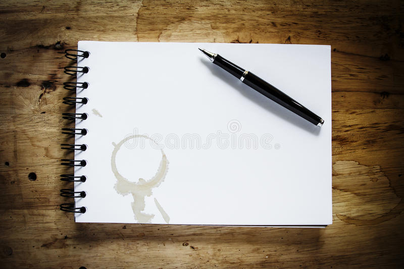 Book with pen. Coffee stain on spiral book with pen on vintage wood table background royalty free stock photos