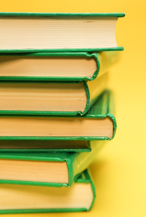Book pile, over a yellow background - Education books background royalty free stock image