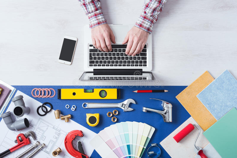 Book a plumber online. Male hands using a laptop next to plumbing work tools, tiles and swatches, online booking and home plumber service stock images