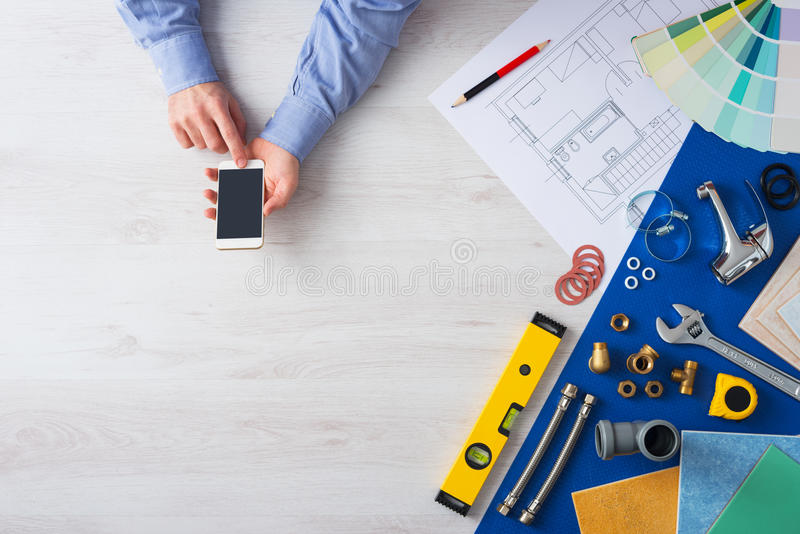 Book a plumber online. Male hands using a mobile phone next to plumbing work tools, tiles and swatches, online booking and plumber service royalty free stock image