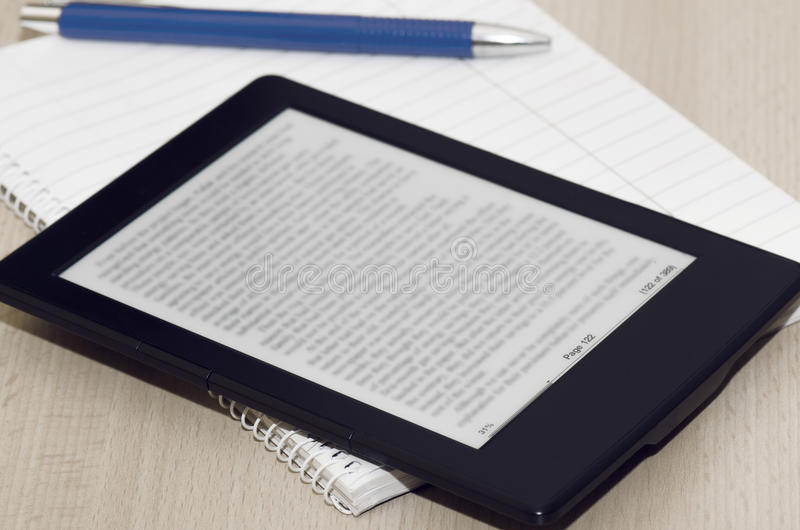 Book Reader With Blurred Text. Electronic Book Reader With Blurred Text On It, White Notebook And Pen Closeup royalty free stock images