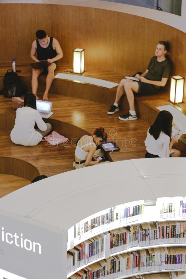 Book readers gather to read in the library in Singapore. royalty free stock photography