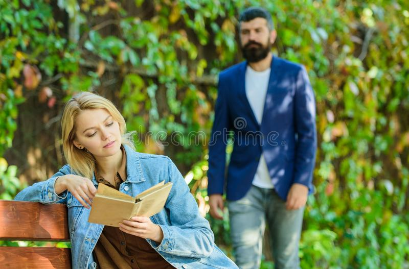 Book reading. spring mood. girl with book on bench. bearded man walk in park. imagination and inspiration. deep in love. Book reading. spring mood. girl with royalty free stock photography