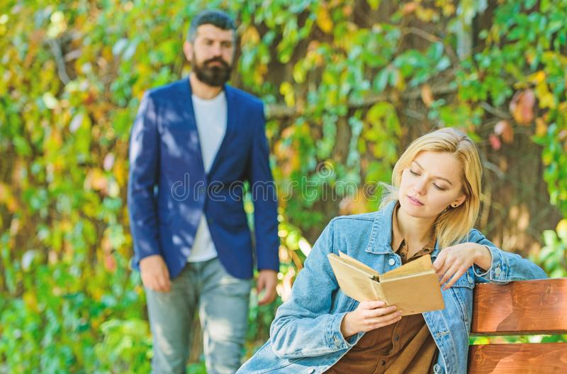 Book reading. spring mood. girl with book on bench. bearded man walk in park. imagination and inspiration. deep in love. Book reading. spring mood. girl with stock photos