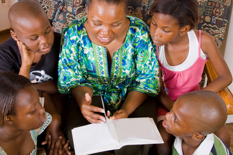 Book reading time. A happy african mother reading a book to her 4 children in living room