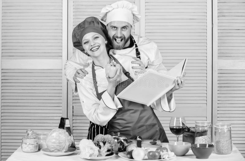 Book recipes. Helpful culinary book. Woman chef and man cooking food together. Culinary family concept. Couple in love royalty free stock photos