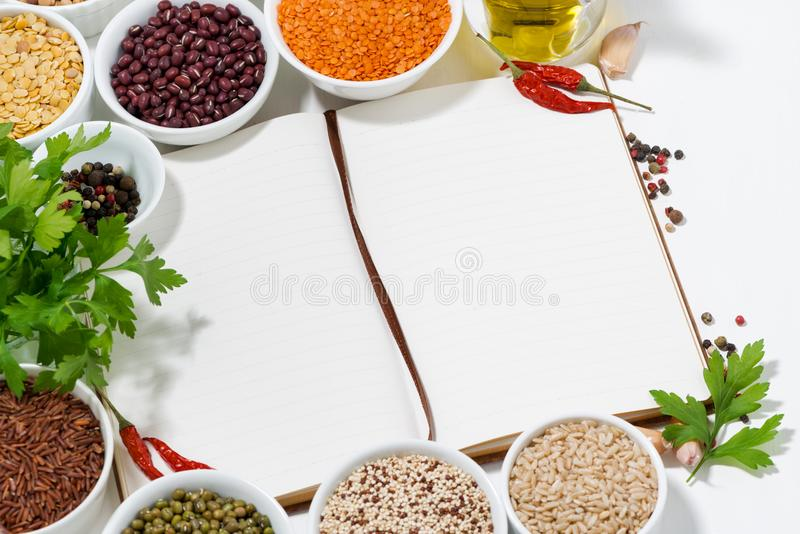 Book for recipes, spices and assortment of legumes. Closeup stock photography