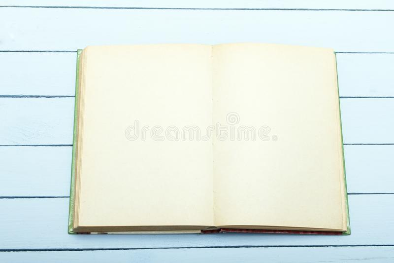 Book scetch with empty sheet on blue wooden table. Draft for advertising, announcement. Top view. royalty free stock photo