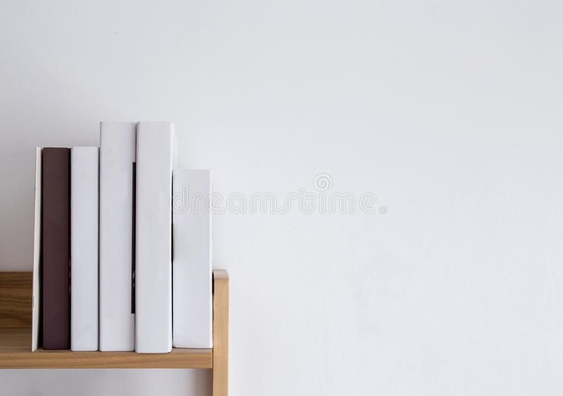Book shelf blank spines, empty binding stack on wood texture background stock images
