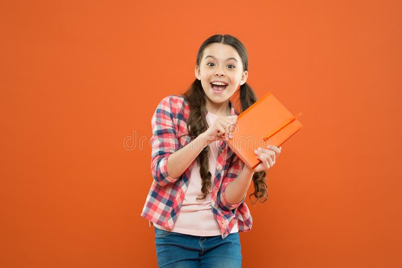 Book shop. school girl read book on orange background. literature lesson. back to school. happy little girl with stock photos