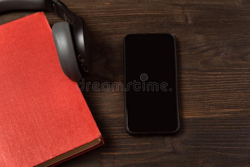 Book, smartphone and headphones on the table. Electronic and audio books in your phone concept. Wooden background.  stock images