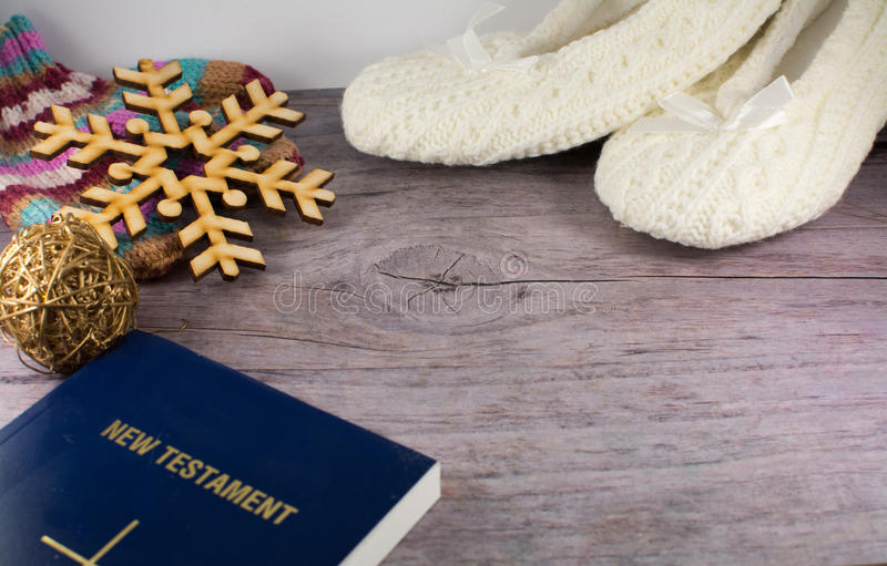 Book, snowflake, knitted socks and mittens, bible on wooden back stock photos