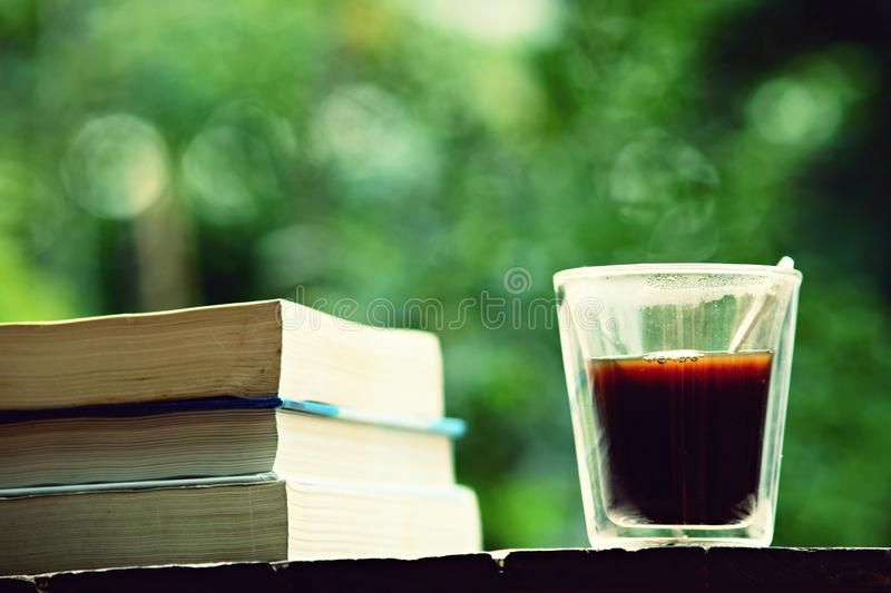 Book stack and cup of coffee on wooden table in vintage tone color, wisdom concept, copy space. Book stack and a cup of coffee on wooden table in vintage tone royalty free stock photo