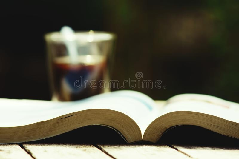 Book stack and cup of coffee on wooden table in vintage tone color, wisdom concept, copy space. Book stack and a cup of coffee on wooden table in vintage tone stock images