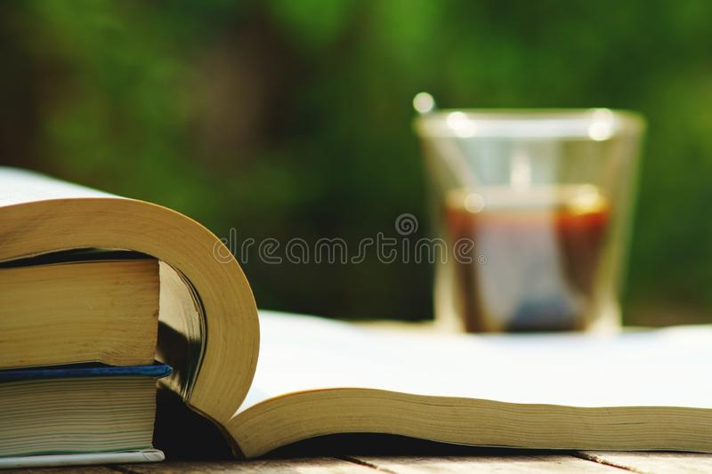 Book stack and cup of coffee on wooden table in vintage tone color, wisdom concept, copy space. Book stack and blur cup of coffee on wooden table in vintage tone royalty free stock photography