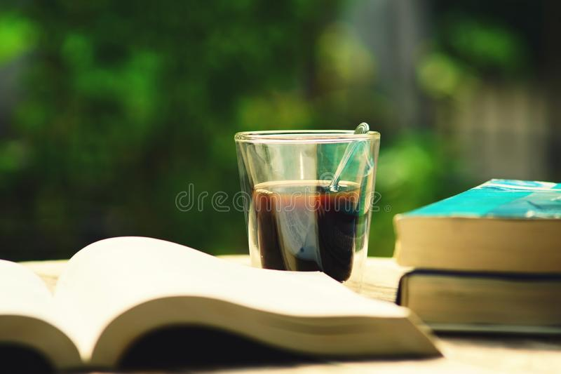 Book stack and cup of coffee on wooden table in vintage tone color, wisdom concept, copy space. Book stack and blur cup of coffee on wooden table in vintage tone stock images