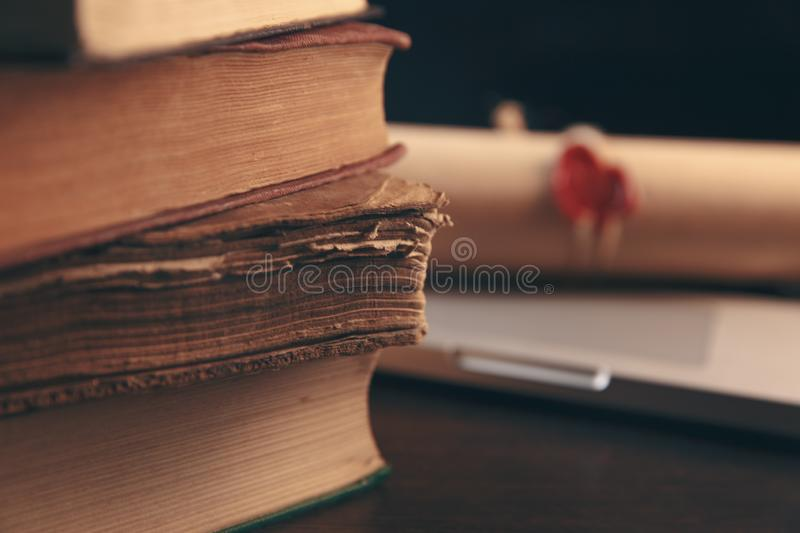 Book stack and laptop computer on workplace in library room with blurred bookshelf background, education concept royalty free stock image