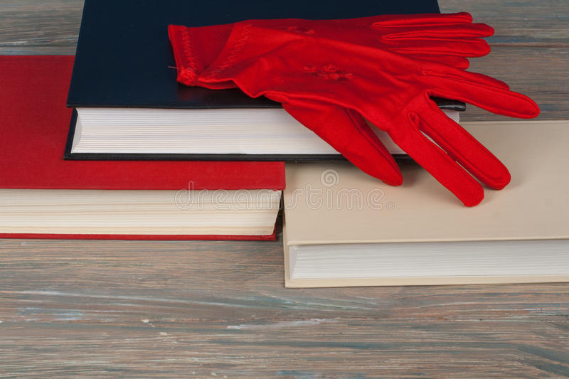 Book stacking. Open book, hardback books on wooden table . Back to school. Copy space for text. Knitted gloves. royalty free stock images