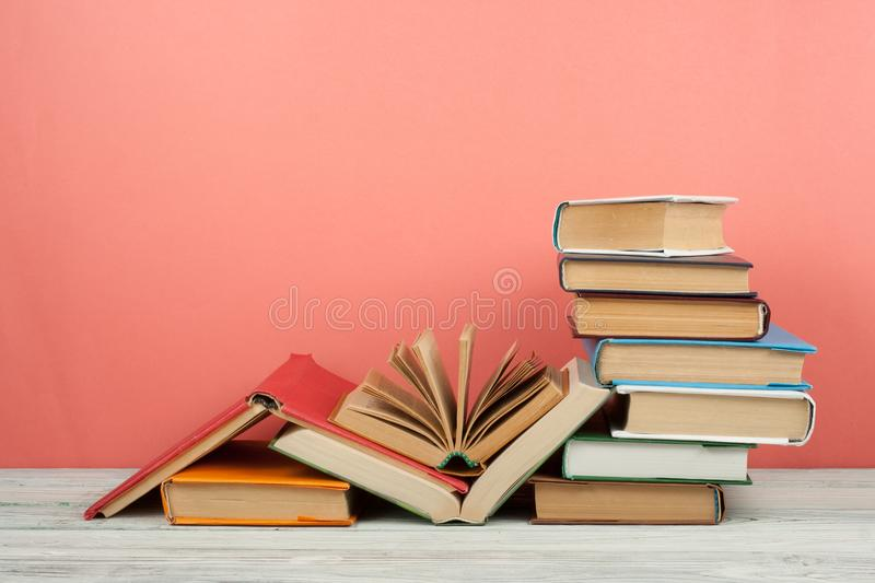 Book stacking. Open book, hardback books on wooden table and pink background. Back to school. Copy space for text stock images