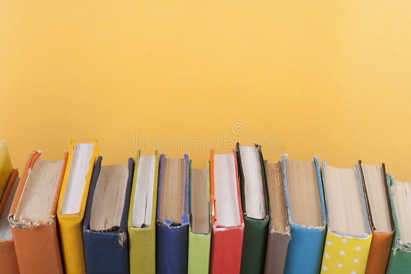 Book stacking. Open hardback books on wooden table and yellow background. Back to school. Copy space for ad text royalty free stock image