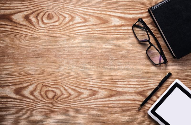 Book, tablet, glasses and pen on wooden table. Ebook concept stock photos