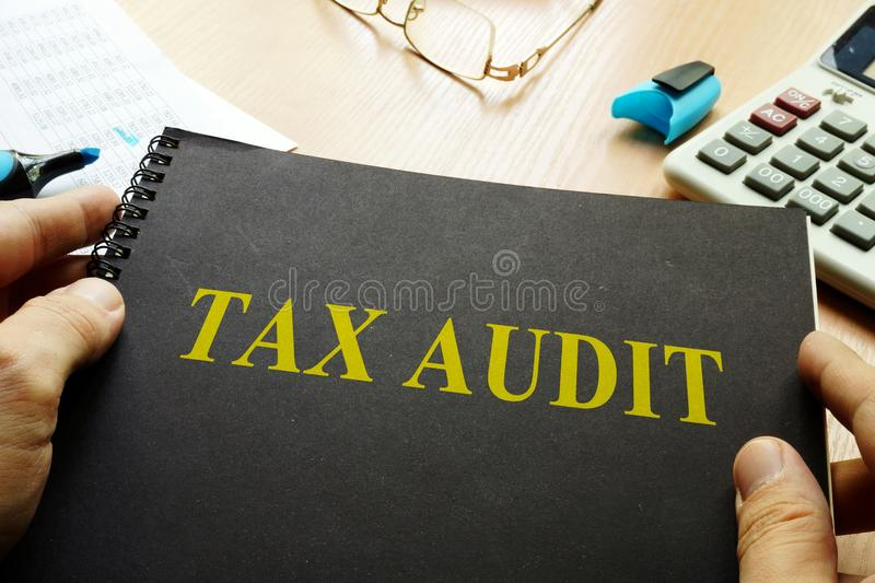 Book about tax audit. Book about tax audit and calculator on a desk stock images