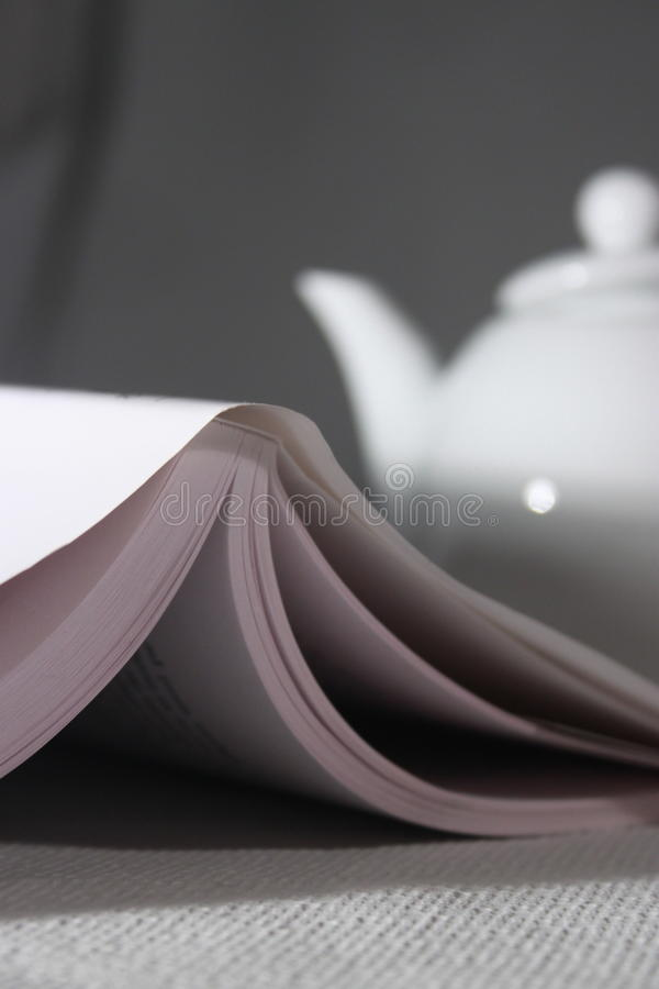 Book and a tea pot. Relaxation time with a book and a tea pot royalty free stock image