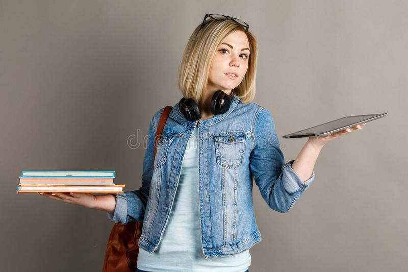 Book vs. e-book. Girl student holding a traditional textbook and royalty free stock photos