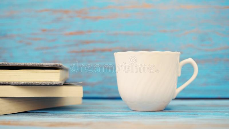 Book & white cup on blue wood background. royalty free stock photos