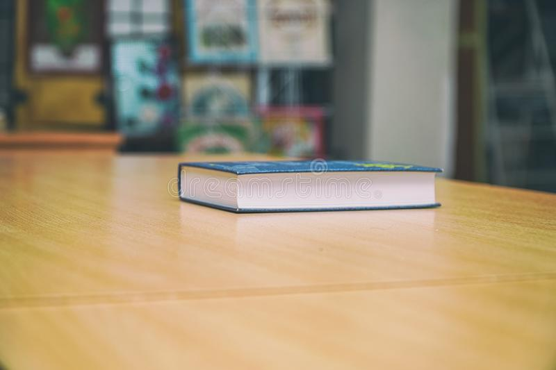 Book on a wooden table on a background of blurred bookshelf. A closed Book on a wooden table on a background of blurred bookshelf royalty free stock image