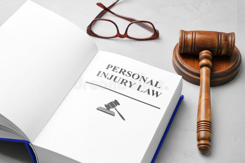 Book with words PERSONAL INJURY LAW,. Gavel and glasses on grey background stock photography