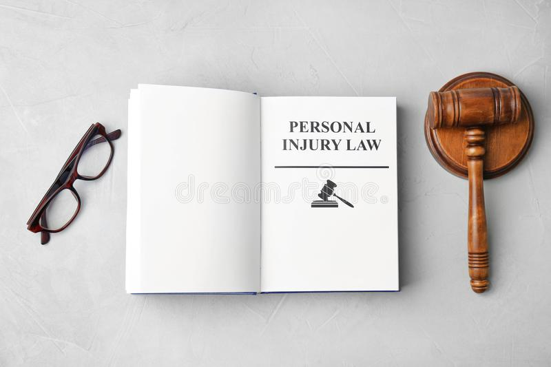 Book with words PERSONAL INJURY LAW. Gavel and glasses on grey background, top view royalty free stock photo